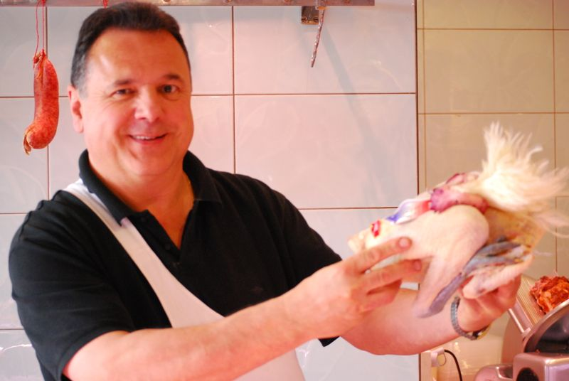 A proud butcher in Louhans showing off his prized Bresse Chicken [Photo by Michael DeMoney]