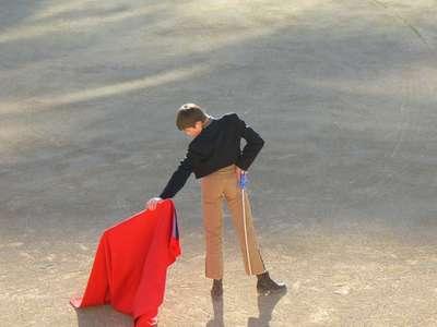 A future bullfighter practicing his craft in Les Arènes de Nîmes